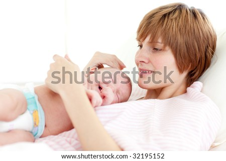Mother attending to her newborn baby in hospital - stock photo
