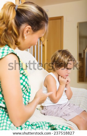 Mother berating  crying daughter at home - stock photo