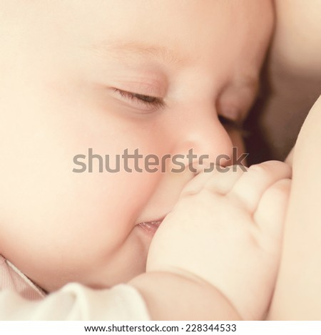 Mother breast feeding her baby with closed eyes - stock photo