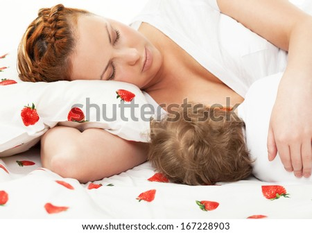 Mother breast feeding her child on the bed - stock photo