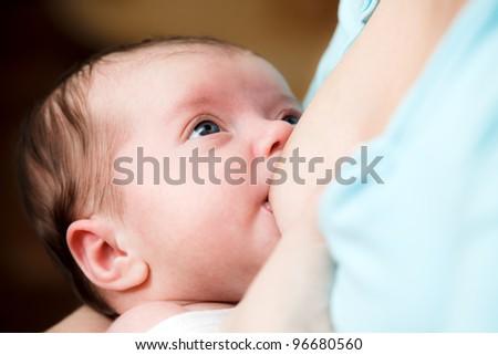 Mother breast feeding newborn baby - stock photo