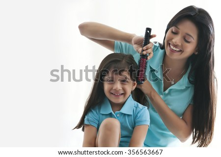 Mother brushing daughters hair - stock photo