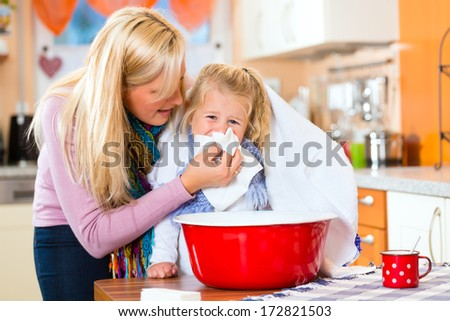 Mother care for sick child with vapor-bath at domestic kitchen  - stock photo