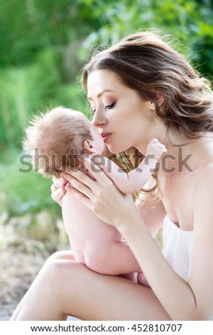 Mother caresses the child on nature. Mother and newborn baby outdoor - stock photo