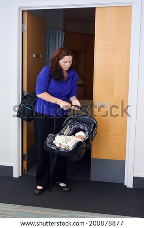 Mother carry her newborn baby in a car seat from hospital, home. - stock photo