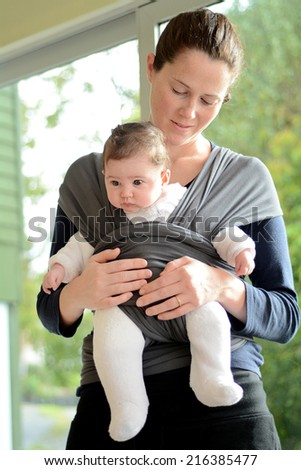 Mother carry here newborn with a baby sling wrap.Concept photo of Newborn baby, mother, motherhood, healthcare, transport, transportation. - stock photo