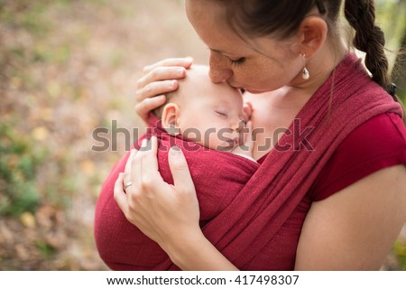 Mother carrying her cute baby daughter in sling, kissing her, outside in autumn nature - stock photo