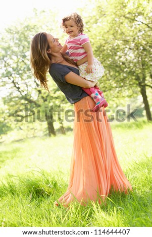 Mother Carrying Young Daughter Through Summer Field - stock photo