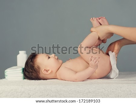 mother changing baby diaper   - stock photo