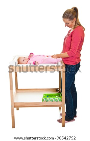 Mother changing little girl's diaper on nursery table - stock photo
