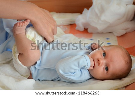 Mother changing the baby's nappy - stock photo
