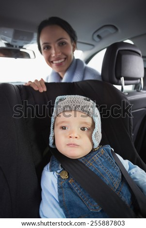 Mother checking her baby in the car seat in her car - stock photo