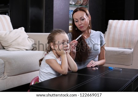 mother checking the temperature  her sick  daughter - stock photo