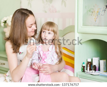 mother checks temperature at the sick child - stock photo
