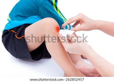 Mother clean and provides first-aid at wound on son leg, shoot in studio, on white background - stock photo