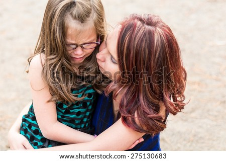 Mother comforting her daughter after getting hurt at a park in Reno, Nevada, USA. - stock photo