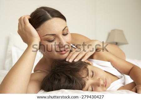 Mother Comforting Sleeping Son In Bed - stock photo
