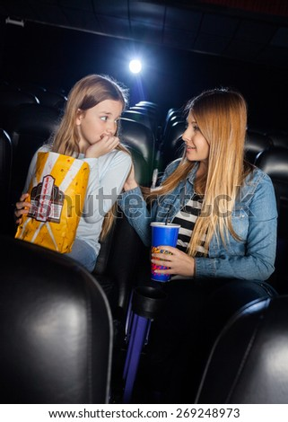 Mother consoling scared daughter while watching movie in cinema theater - stock photo