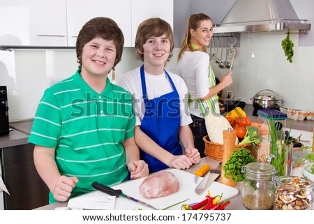 Mother cooking with her sons in the kitchen - family life. - stock photo
