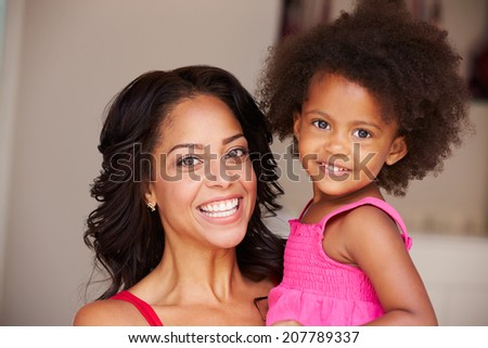 Mother Cuddling Daughter At Home - stock photo