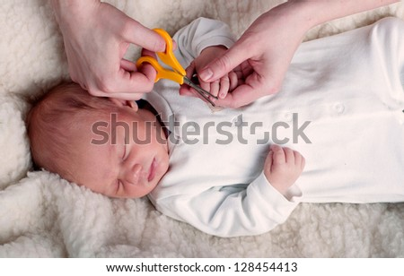 Mother cutting babies nails - stock photo
