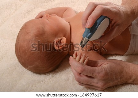 mother cutting baby nails with fingernail clippers - stock photo