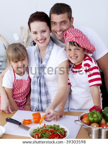 Mother cutting vegetables in kitchen with her family - stock photo