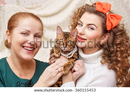 Mother, daughter and a cat. Hugs with a pet. Bengal cat. Cat in the beads. - stock photo
