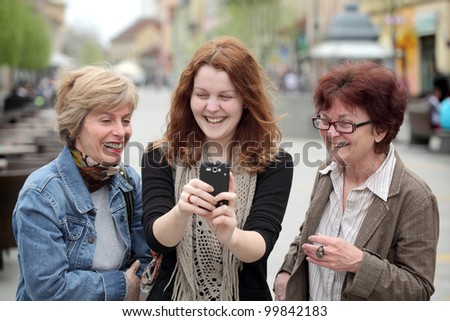 Mother, daughter and aunt looking to mobile phone and laughing - stock photo