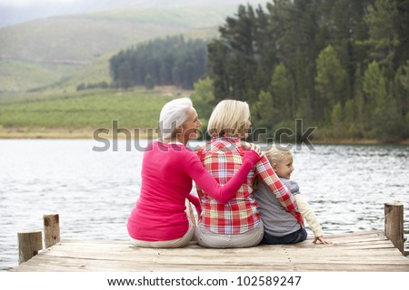 Mother, daughter and grandmother sitting on a jetty - stock photo