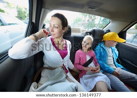 Mother, daughter and son in the back seat of a car - stock photo
