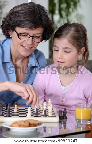 Mother daughter chess match - stock photo