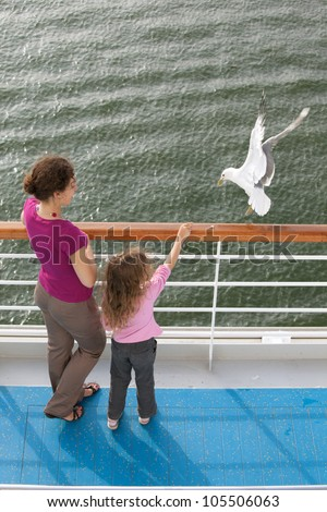 mother daughter traveling boat feed seagulls - stock photo