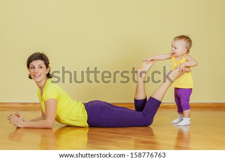 Mother do phisical exercises with her daughter at home - stock photo