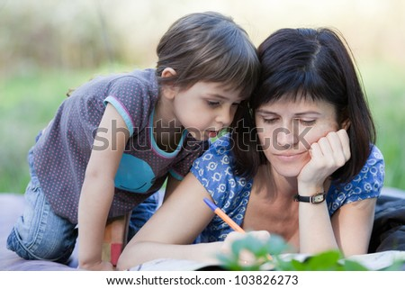Mother doing crossword, little daughter looks at it - stock photo