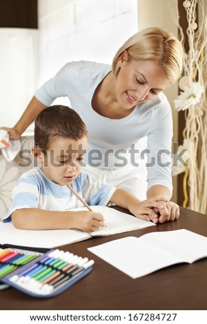 Mother doing homework with her son - stock photo