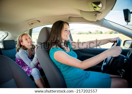 Mother driving car and child sitting on back seat - no belt, dangerous - stock photo