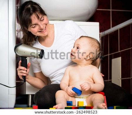 Mother drying hair of her child with hairdryer in bathroom - stock photo