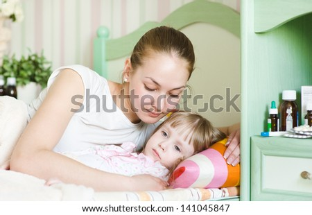 mother embraces the sick child - stock photo
