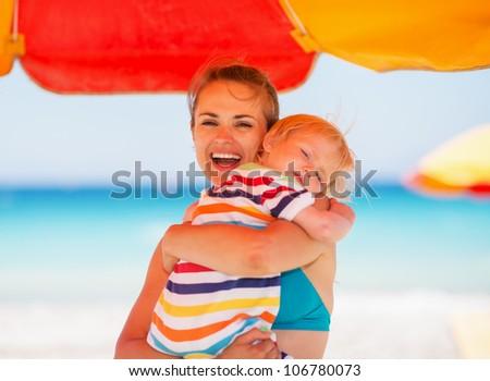 Mother embracing baby on beach under umbrella - stock photo