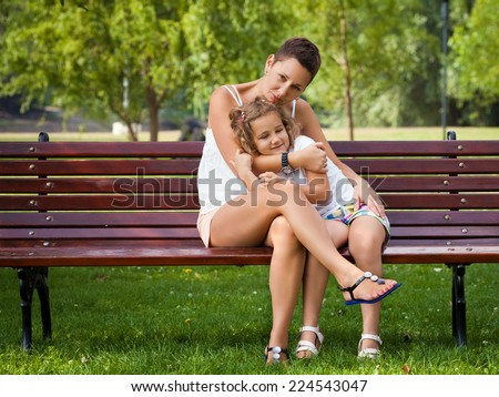 Mother embracing  her little daughter while sitting on a bench in nature. - stock photo