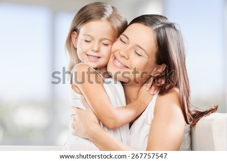 Mother. Family, child and happiness concept - hugging mother and daughter - stock photo