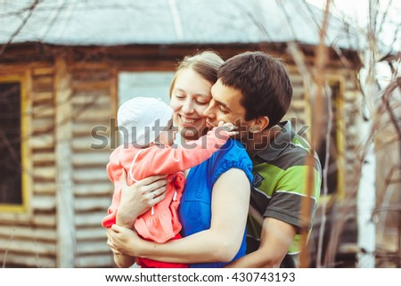 Mother, father and baby daughter hugging and smiling. - stock photo