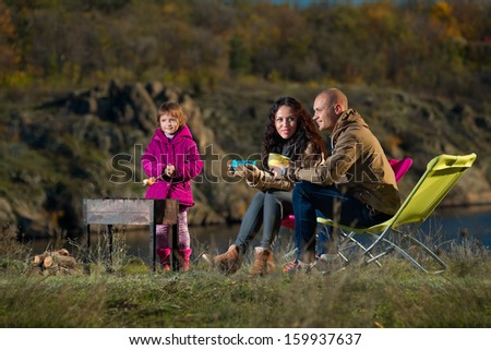 Mother, father and  child having rest outdoor - stock photo