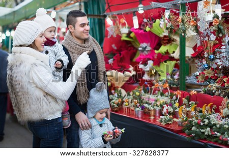 Mother, father and children buying red Euphorbia at Christmas fair. Focus on woman - stock photo