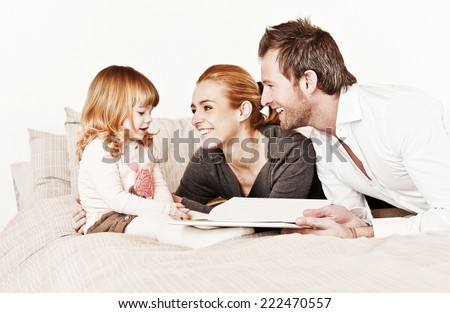 Mother, father and daughter reading a book together. - stock photo