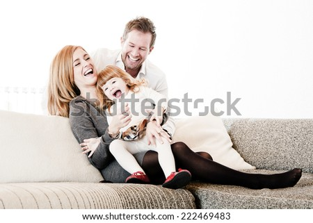 Mother, father and daughter sitting on the sofa & watching a Movie on TV. - stock photo