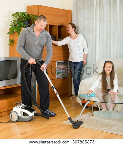 Mother, father and happy little american girl doing general cleaning indoors - stock photo