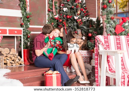 mother father and son sitting near xmas tree with gifts - stock photo