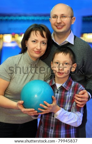 Mother, father and son, stand alongside and hold one ball for bowling - stock photo